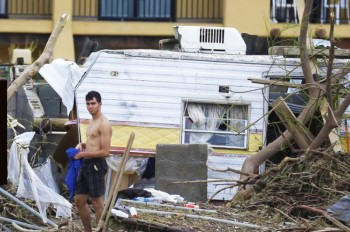 A man stands by a trailer that was swept along with debris, by the flood waters and high winds of Hurricane Odile in Los Cabos, Mexico, Monday, Sept. 15 2014. Hurricane Odile blazed a trail of destruction through Mexico's Baja... - The Associated Press.
